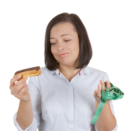 Diet Concept. Beautiful Pretty Young Woman Choosing Between Chocolate Eclair and Health Life with Measuring Tape on a white background Stock Photo