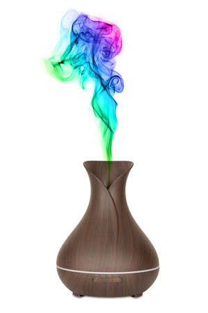 Aromatherapy Concept. Wooden Electric Ultrasonic Essential Oil Aroma Diffuser and Humidifier with Colour Steam on a white background Stock Photo