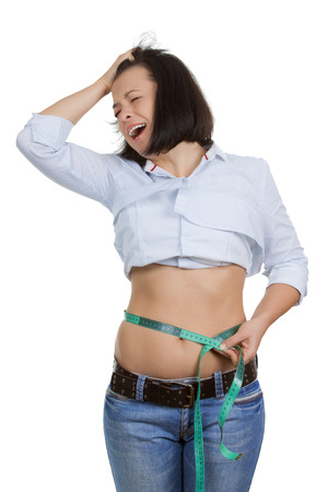 Weight Loss and Healthy Lifestyle Concept. Fitness Woman in Shock Measuring Her Waistline with Measure Tape extreme closeup