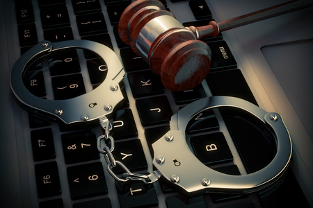 Cyber Crime Concept. Handcuffs and judge gavel on Laptop Computer extreme closeup. 3d Rendering Stock Photo