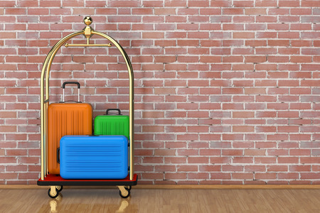 Large Multicolour Polycarbonate Suitcases in Golden Luxury Hotel Luggage Trolley Cart in front of brick wall. 3d Rendering Stock Photo