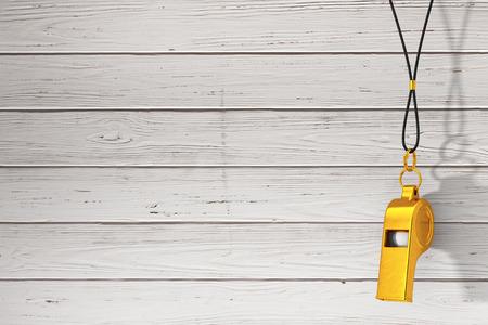 Los entrenadores de metal dorado clásico silbato colgando de una cuerda roja sobre un fondo de tablas de madera. Representación 3D