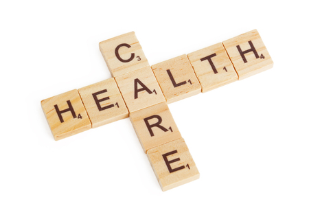 Health Care Concept. HEalth Care Sign as Crossword Wooden Blocks on a white background