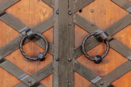 Old Wooden Door with Circle Iron Door Handle Knocker extreme closeup.
