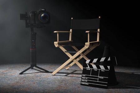 Concetto di industria cinematografica. Sistema treppiede di stabilizzazione cardanica DSLR o videocamera vicino alla sedia da regista, al batacchio di film e al megafono nella luce volumetrica su uno sfondo nero. Rendering 3D Archivio Fotografico