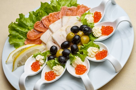 plating: Overhead view of a smoked salmon and cheese platter served with fresh lettuce and garnished with lemon wedges Stock Photo