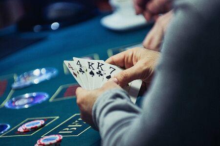 casinò, gioco d'azzardo, poker, le persone e concetto di intrattenimento - vicino di giocatore di poker con carte da gioco e fiches al tavolo verde casinò durante le vacanze luci sfondo