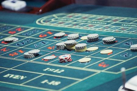 Particolare di un tavolo di roulette verde con alcuni numeri.