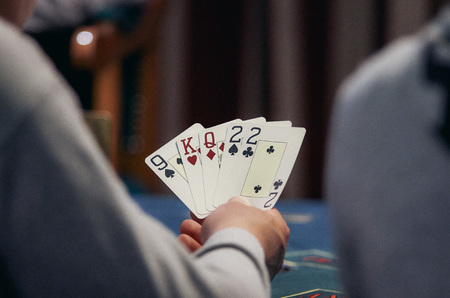 hold em: casino, gambling, poker, people and entertainment concept - close up of poker player with playing cards and chips at green casino table over holidays lights background Stock Photo