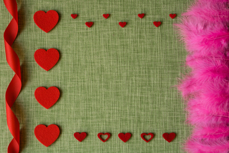 Felt heart and dyed bird feathers on fabric background, Valentines card
