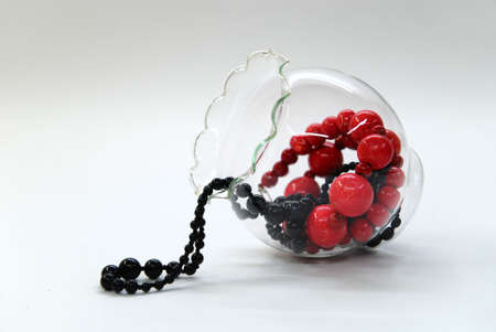 Red and black shining beads in a glass bowl Stock Photo