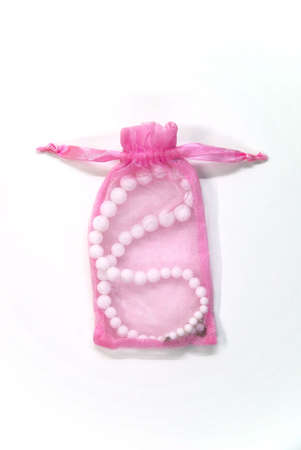 small pink bag with pearl on a white background Stock Photo