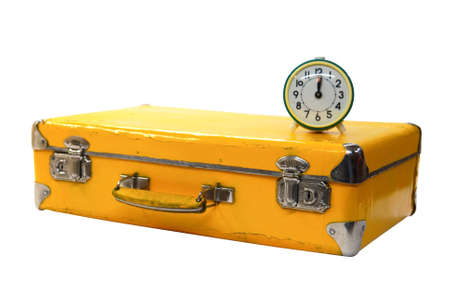 old yellow suitcase with green alarm clock on a white