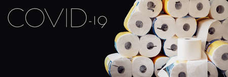 COVID-19 header for webseite, banner, horizontal poster with dark background. A large stack of white paper rolls packages. World wide toilet paper crisis related to the outbreak of the coronavirus. Banque d'images