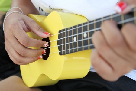 Closeup of a woman playing ukulele. photo