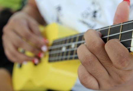 Closeup of a woman playing ukulele. Stock Photo