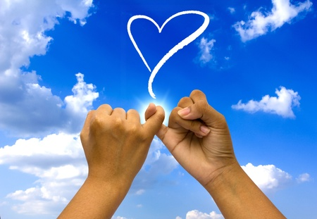 Two coupled hands on blue sky. Stock Photo