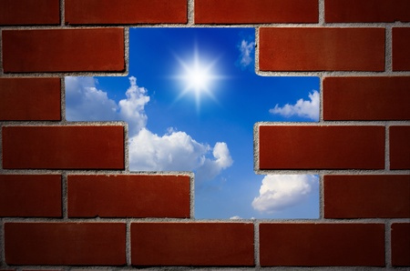 Brick wall and blue sky with clouds and sun. Stock Photo - 10966299