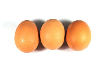 Three brown eggs isolated on white background. photo