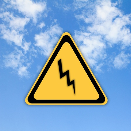 Danger high voltage sign on beautiful sky background. photo