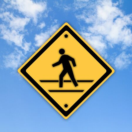 Crosswalk sign with a man walking on yellow with a blue sky background Stock Photo