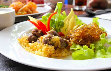 Thai food, rice in cold water served with fried sweet pork,fried egg and vegetable (khao chae) Stock Photo
