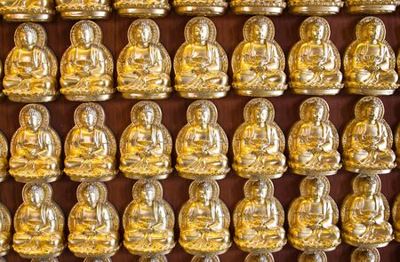Many small Buddha statue on the wall at chinese temple, Thailand photo