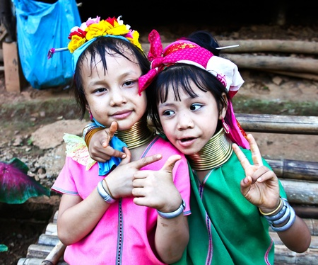 CHIANG RAI, THAILAND - AUGUST 25: Unidentified Karen tribe girls poses for the camera in Chiang Rai on August 25, 2012. The Karen people wear brass rings around their neck from as young as five years old.