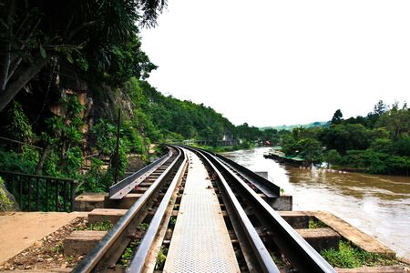 Dead railway beside cliff, along Kwai river in Thailand photo