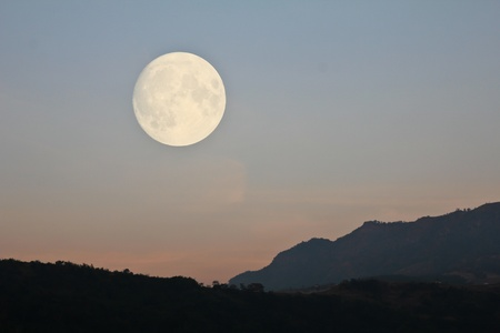 Big Moon over mountain in morning light.
