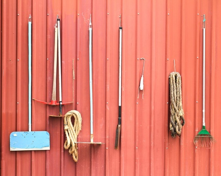 Farm tools hang on red barn wall Stock Photo - 21796861