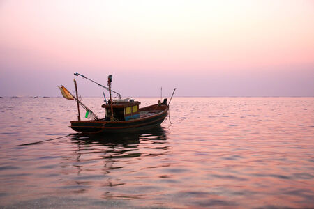Fishing boat at sunset photo
