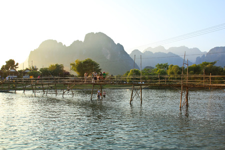 VANG VIENG, LAOS - FEB 1: Local people and tourists cross the bamboo bridge at sunset on February 1, 2014 in Vang Vieng, Laos. Vang Vieng is a tourism-oriented town in Laos, about four hours bus ride north of the capital.
