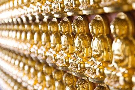 Ten Thousand Golden Buddhas lined up along The wall of Chinese Temple in Thailand. photo
