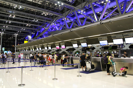 BANGKOK - AUGUST 15 : People waiting in check-in line K terminal of the Bangkok airport on August 15, 2014. Suvarnabhumi airport is worlds 4th largest single-building airport terminal.