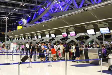 suvarnabhumi: BANGKOK - AUGUST 15 : People waiting in check-in line K terminal of the Bangkok airport on August 15, 2014. Suvarnabhumi airport is worlds 4th largest single-building airport terminal. Editorial