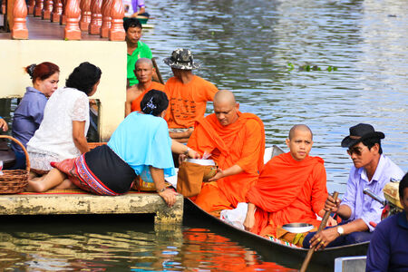 NONTHABURI, THAILAND - November 6 : Buddhist monk is the alms on morning at Sai Noi Floating Market on November 6,2014 in Sai Noi, Nonthaburi province, Thailand.