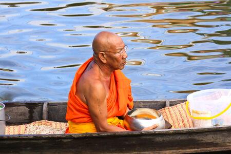nonthaburi province: NONTHABURI, THAILAND - November 6 : Buddhist monk is the alms on morning at Sai Noi Floating Market on November 6,2014 in Sai Noi, Nonthaburi province, Thailand.