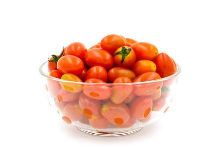 Tomates cerises dans un bol en verre sur fond blanc.
