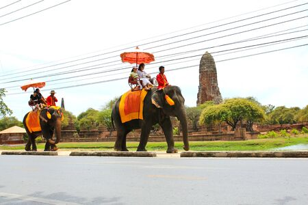 ancient elephant: AYUTTHAYA, THAILAND - JULY 23: Tourists on an elephant ride tour of the ancient city on July 23, 2015 in Ayutthaya.