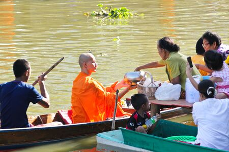 NONTHABURI, THAILAND - November 25 : Buddhist monk is the alms on morning at Sai Noi Floating Market on November 25,2015 in Sai Noi, Nonthaburi province, Thailand.
