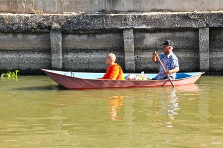 alms: NONTHABURI, THAILAND - November 25 : Buddhist monk is the alms on morning at Sai Noi Floating Market on November 25,2015 in Sai Noi, Nonthaburi province, Thailand.