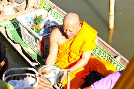 nonthaburi province: NONTHABURI, THAILAND - November 25 : Buddhist monk is the alms on morning at Sai Noi Floating Market on November 25,2015 in Sai Noi, Nonthaburi province, Thailand.