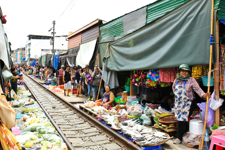 SAMUT SONGKHRAM, THAILAND - SEPTEMBER 4,2016 : The famous railway market or folding umbrella market at Samut Songkhram, Thailand, A famous market in Thailand and sixth times a day the train runs through these stalls.
