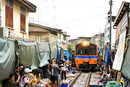 SAMUT SONGKHRAM, THAILAND - SEPTEMBER 4, 2016 : Mae Klong Market placed all product on railroad, all vendors have to move product away when the train passes market.