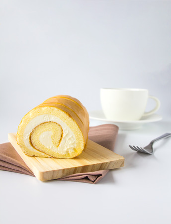 Swiss roll and coffee on white background.