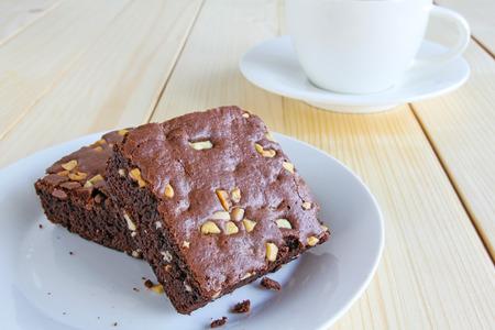 チョコレートブラウニーと木製の背景に熱いブラック コーヒー カップ