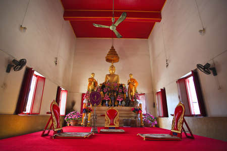 Buddha statue in the temple and fan as background