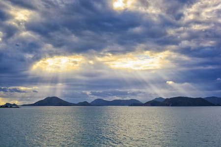jesus clouds: blue sky with sun and beautiful clouds and island Stock Photo
