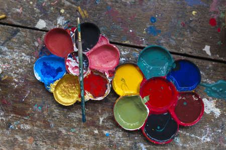 art palette with blobs of paint and a brush on wooden background photo